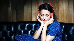 young woman listening to music wearing headphones