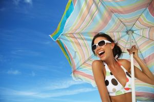 Young-woman-holding-beach-umbrella-smiling-close-up