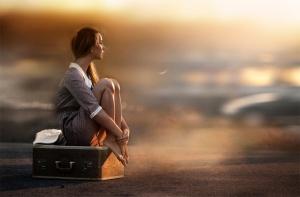 elena-shumilova-femme-assise-sur-ses-valises-au-bord-dune-route