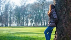 stock-footage-woman-in-jacket-resting-leaning-on-tree-person-in-forest-park-with-green-lawn-in-the-middle